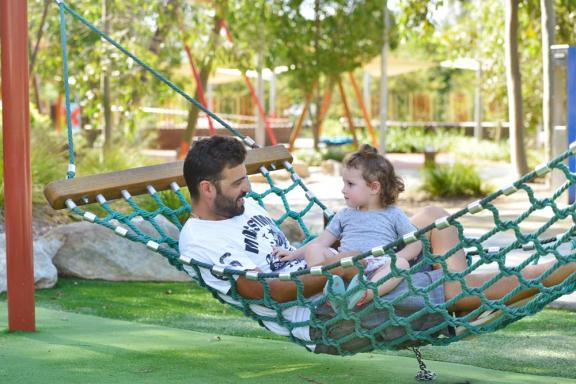 Father and daughter in a hammock swing at the playground