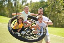 Kids on a basket swing with adult pushing them