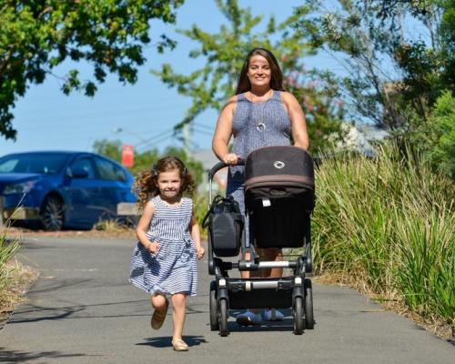 child running and mother pushing pram